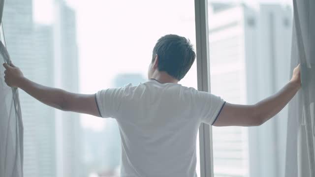 vídeos de stock, filmes e b-roll de um homem asiático acorda de manhã e se levanta da cama para abrir uma cortina na janela do quarto para ver a cidade pela janela da manhã. - estação turística