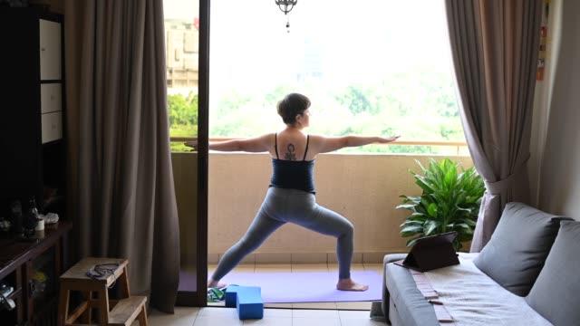 vídeos de stock, filmes e b-roll de uma mulher asiática média adulta treino yoga na varanda de casa durante a ordem de movimento restrito na malásia com classe on-line guerreiro 2 pose - varanda