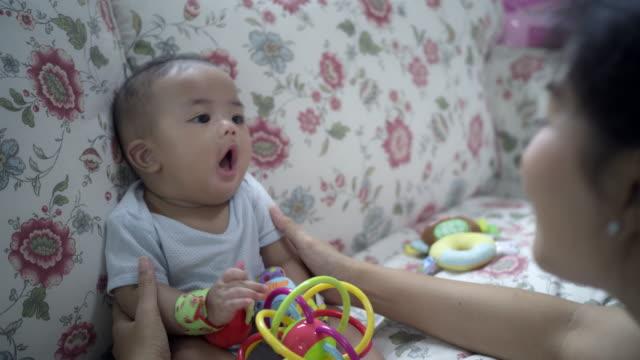 vídeos y material grabado en eventos de stock de una madre soltera asiática está jugando con su hijo en el sofá sala de estar en casa - son