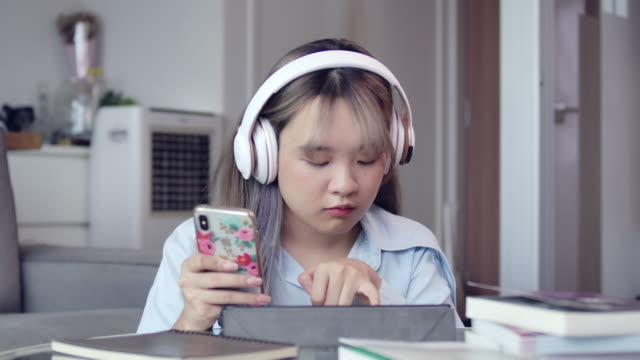 an asian teenager girl with long hair is learning home online study in the living room during the covid quarantine. - hot desking stock videos & royalty-free footage