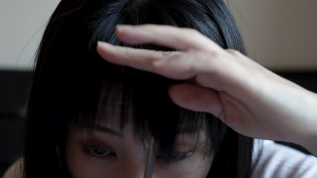 an asian woman cutting her own bangs at home. - bangs stock videos & royalty-free footage