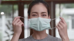 An Asian woman in a casual dress is pulling the mask off her face and smiling at the camera. Conveys the improved situation of COVID-19 People began to smile again.