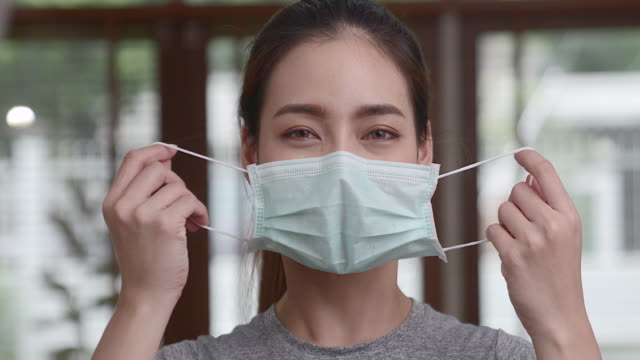 an asian woman in a casual dress is pulling the mask off her face and smiling at the camera. conveys the improved situation of covid-19 people began to smile again. - removing stock videos & royalty-free footage