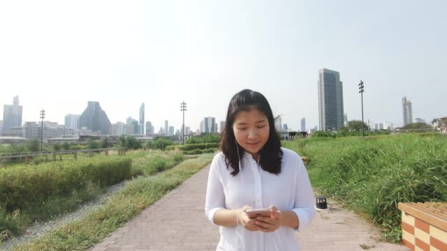 an asian woman in public park. - black hair stock videos & royalty-free footage