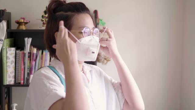 stockvideo's en b-roll-footage met een aziatische vrouw gaat werken. ze draagt een n95 masker om te beschermen tegen stof en virussen. - kwaliteit
