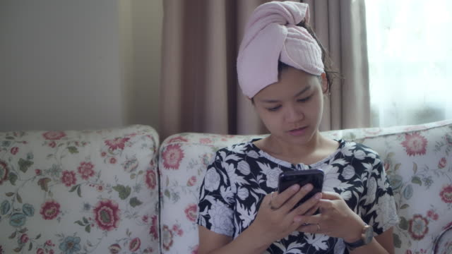 An asian woman using a phone at home indoor