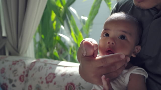 an asian young father sitting, carrying a child and playing with his baby boy in the living room at home - genderblend stock videos & royalty-free footage