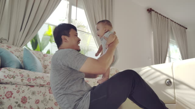 an asian young father sitting, carrying a child, doing exercise, playing with his baby boy in the living room at home - genderblend stock videos & royalty-free footage