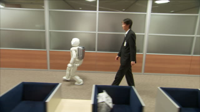 an asimo humanoid leads a business professional through a conference hall. - ホンダ点の映像素材/bロール