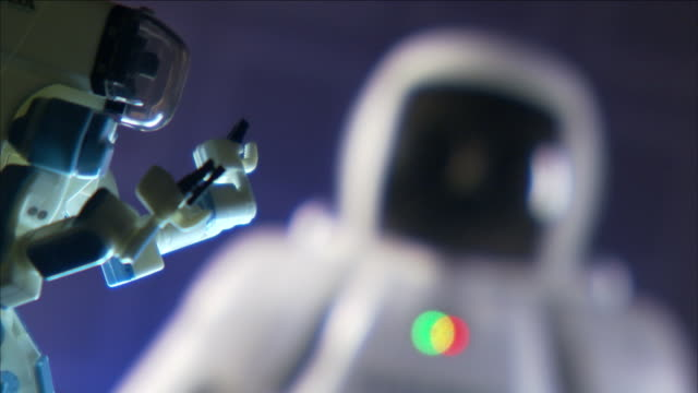 an asimo humanoid waves its hands near another robot. - asimo stock videos & royalty-free footage