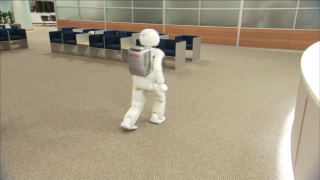 an asimo robot steps and turns in a lobby near a reception desk. - cyborg video stock e b–roll