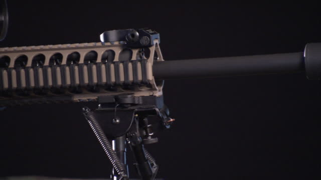 an assault rifle is equipped with a suppressor and scope. - fadenkreuz stock-videos und b-roll-filmmaterial