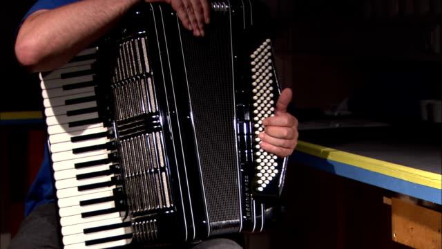 vídeos de stock e filmes b-roll de an assembler tests the bellows and valves of an accordion. - acordeão instrumento
