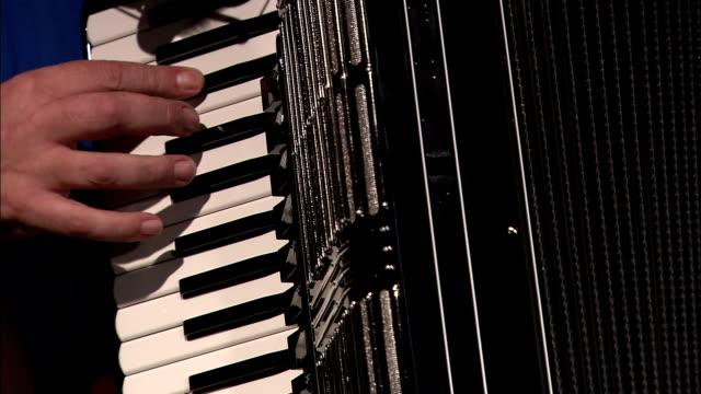 vídeos de stock e filmes b-roll de an assembler tests the treble keyboard of an accordion. - acordeão instrumento