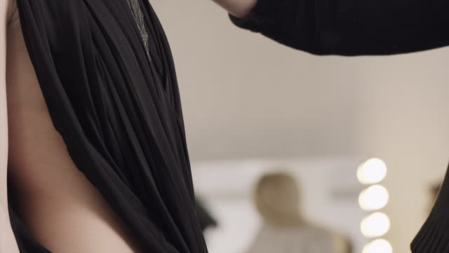 stockvideo's en b-roll-footage met an assistant holds a necklace up to a model in a dressing room. - designerkleding