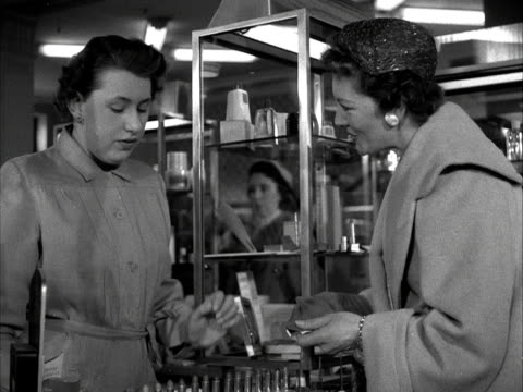 an assistant on a beauty counter in a department store, advises a customer on shades of lipstick to match her gloves. 1955. - department store stock videos & royalty-free footage