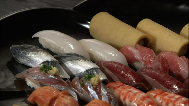 an assortment of nigiri sushi sit on a platter. - nigiri stock videos and b-roll footage