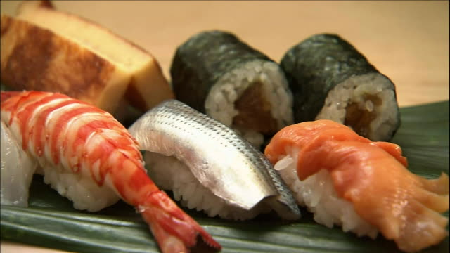 an assortment of sushi lie on bamboo grass. - nigiri stock videos and b-roll footage