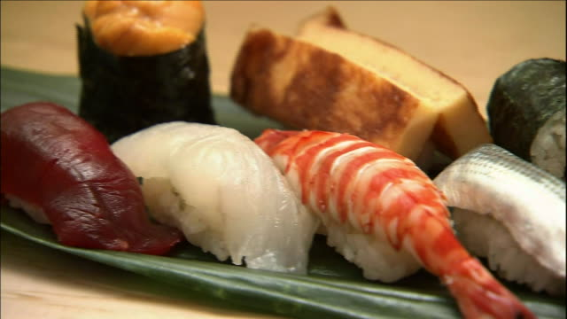 an assortment of sushi lies on bamboo grass. - nigiri stock videos and b-roll footage