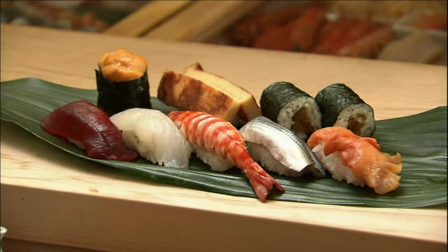 an assortment of sushi lies on the counter of a sushi shop. - nigiri stock videos and b-roll footage
