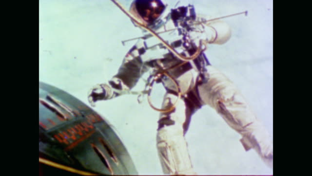 an astronaut in space floats by tethered to ship by rope as narrator ricardo montalban discusses opportunities - spacewalk stock videos & royalty-free footage
