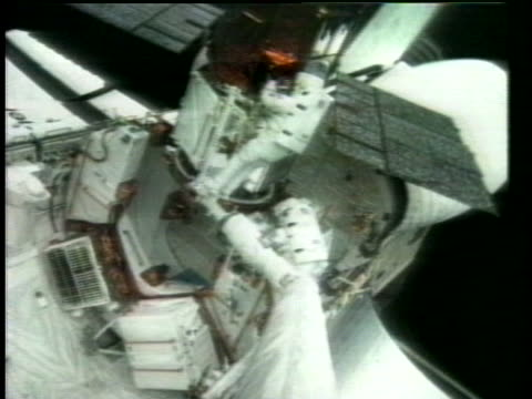 an astronaut in space replaces a part on a solar maximum mission satellite. - repairing stock videos & royalty-free footage