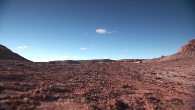 an astronaut rides a four-wheeler in a desert. - weltraumforschung stock-videos und b-roll-filmmaterial