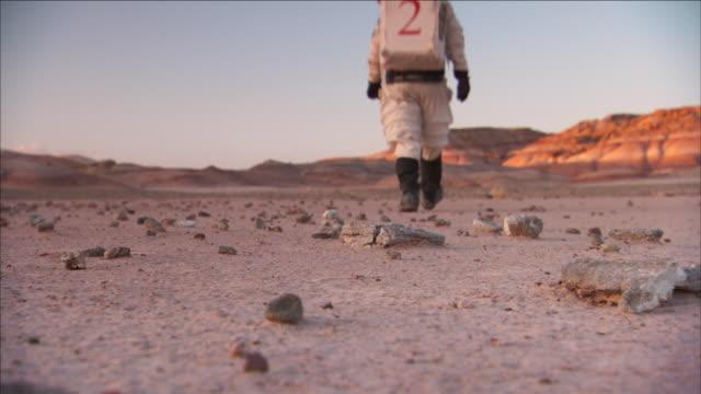 an astronaut walks across a martian desert. - astronaut stock videos & royalty-free footage