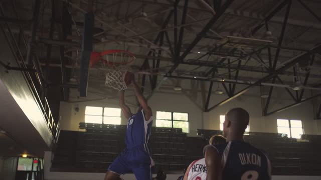SLO MO. An athlete catches a rebound and passes to his teammate who dribbles down court and assists an alley-oop.