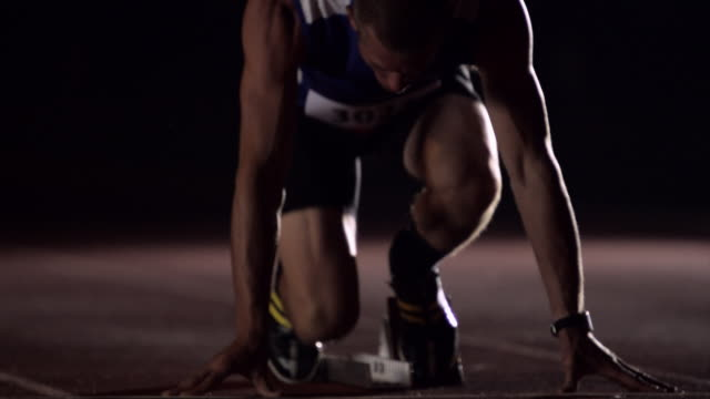 An athlete crouches at the starting blocks on a track before running and practicing jumping jacks.