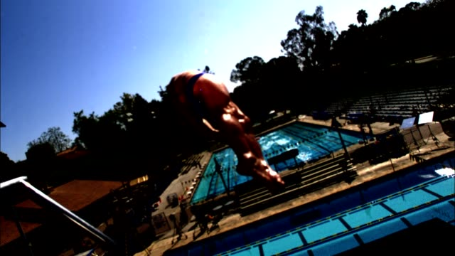 an athlete dives backwards into a pool in slow motion. - 生理学点の映像素材/bロール