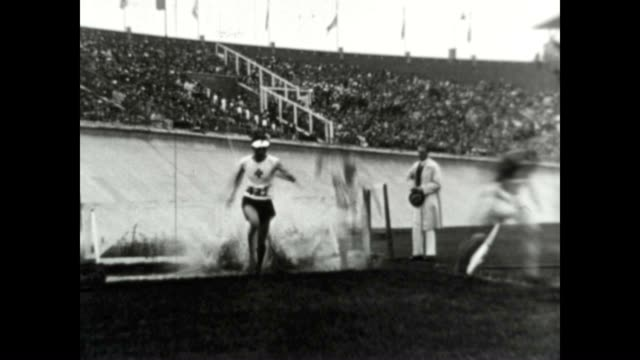 vídeos y material grabado en eventos de stock de an athlete falls to the ground during the olympic steeplechase in amsterdam. in the olympic spirit of sportsmanship, the fellow athlete is helped to... - 1928