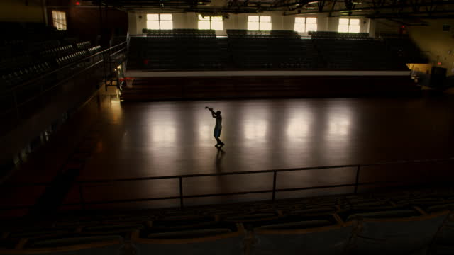 an athlete jogs onto the basketball court, shoots and scores. - コート点の映像素材/bロール