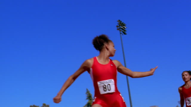 an athlete passes a baton to another runner in a relay race. - stab stock-videos und b-roll-filmmaterial