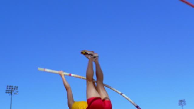 vídeos y material grabado en eventos de stock de an athlete pole vaults. - atlético