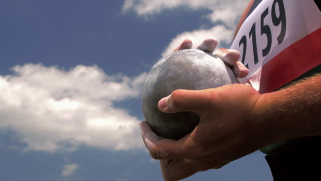 An athlete rubs his chalky hands over a shot put ball.