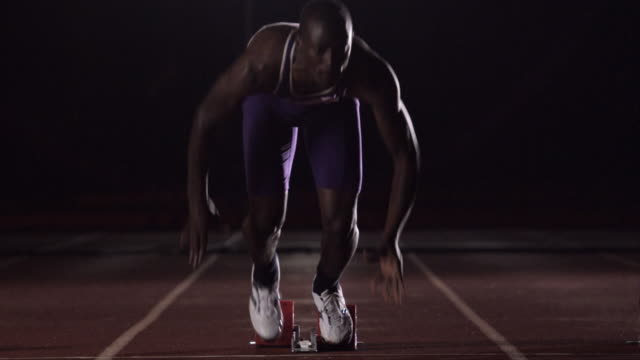 An athlete runs along a track after crouching in the starting position.