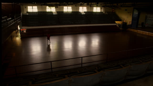 an athlete runs onto the basketball court, shoots and rebounds. - コート点の映像素材/bロール