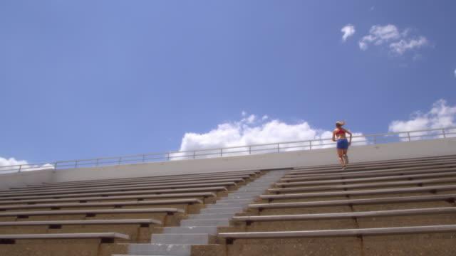 An athlete runs up a flight of bleacher stairs.