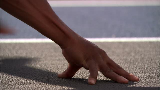 an athlete seeks proper hand position before a sprint. - running track stock videos & royalty-free footage