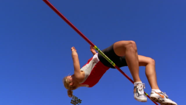 an athlete successfully clears the high jump bar at a track and field event. - athlete stock videos & royalty-free footage
