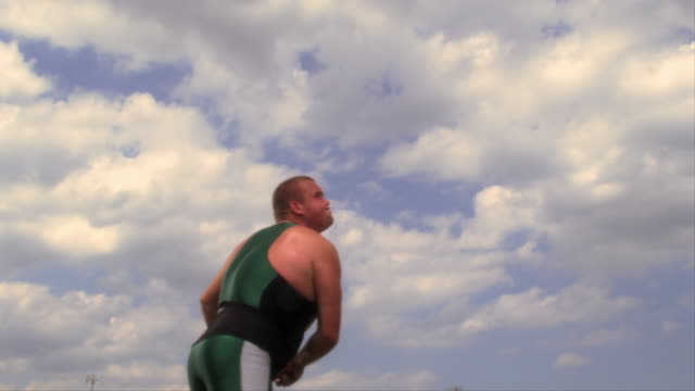 An athlete throws a javelin through the sky.
