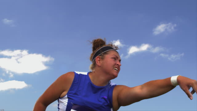 An athlete throws a shot put ball and jumps while watching it fly through the air.