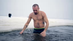 An athlete tries to get accustomed to freezing water.