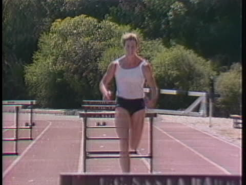 stockvideo's en b-roll-footage met an athletes jumps over hurdles on a track. - sport