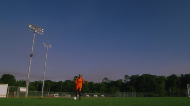 slo mo. an athletic female soccer player runs toward the camera dribbling a soccer ball while running drills on an empty soccer field - soccer competition stock videos & royalty-free footage