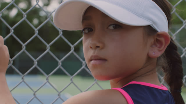 vídeos de stock e filmes b-roll de slow mo. cu. an athletic little girl looks at the camera while watching her female role models play tennis through a chainlink fence - cerca