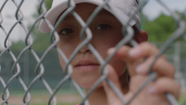 slow mo. cu. an athletic little girl looks into the camera through a chainlink fence while watching her favorite female athletes - recinzione video stock e b–roll