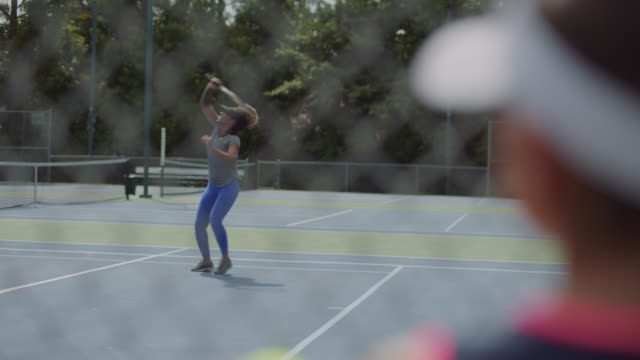 an athletic little girl watches a female tennis player laugh after missing a shot - tennis ball stock videos & royalty-free footage