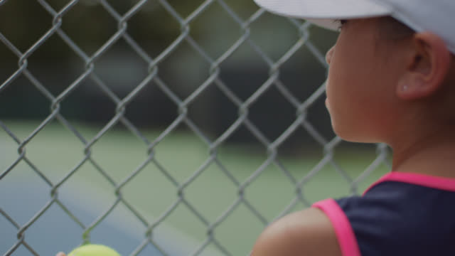 vidéos et rushes de slow mo. cu. an athletic little girl watches her female role models play tennis through a chainlink fence - concentration